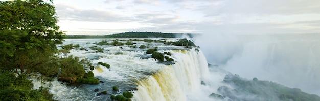 Большая панорама природы каскада водопадов игуасу (игуасу) на границе бразилии и аргентины. удивительный вид на водопад катаратас в ясную солнечную погоду. концепция путешествия. авторские права на сайт