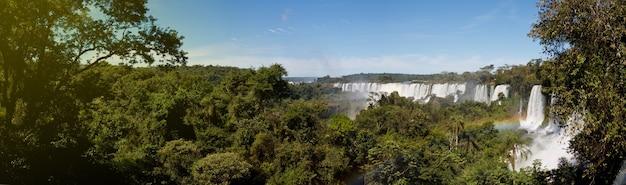 Большая панорама природы каскада водопадов игуасу (игуасу) на границе бразилии и аргентины. удивительный вид на водопад катаратас в ясную солнечную погоду