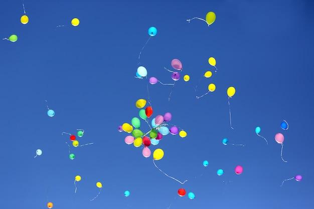 Большое количество разноцветных шаров на фоне голубого неба.