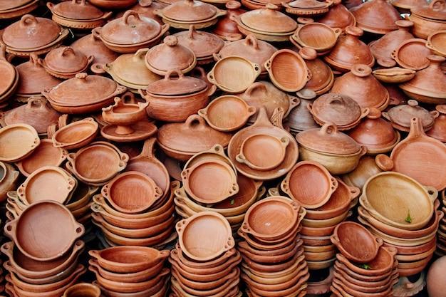 Большое количество глиняной посуды продается на улицах марокко. глиняные тарелки национальных блюд таджин. изготовление керамики вручную мастерами
