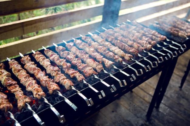 Большое количество готовится шашлык на мангале с углями и копчением под навесом