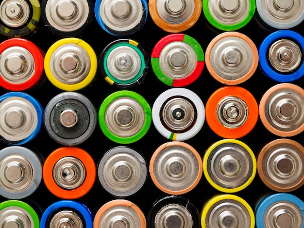 A large number of old aa batteries of different colors