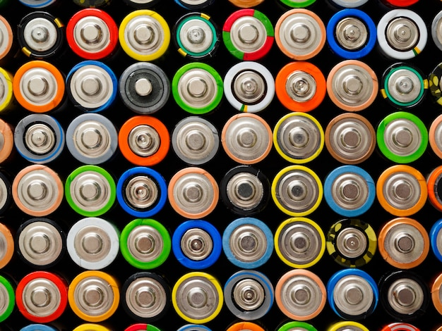 A large number of old aa batteries of different colors.