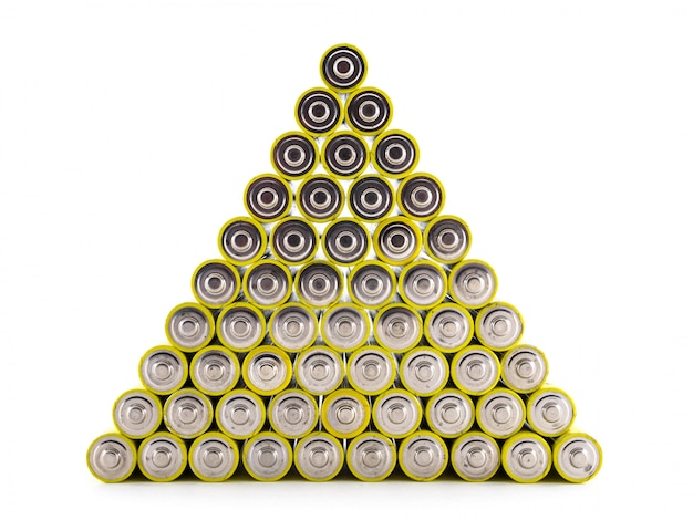 A large number of old aa batteries of yellow color are built in the form of a pyramid. batteries