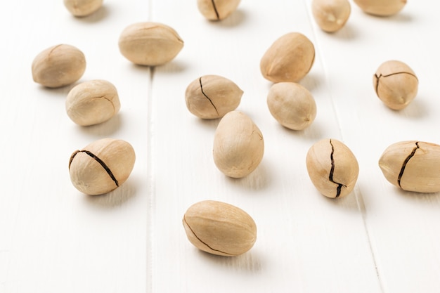 A large number of pecans are scattered on a white wooden table. vegetarian food.