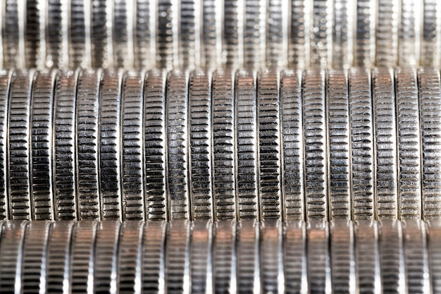 A large number of round metal coins of silver color stacked together in a pile, legal tender that is used for payments in the state, beautiful coins close-up the same coin value