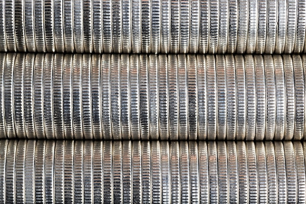 A large number of round metal coins of silver color stacked together in a pile