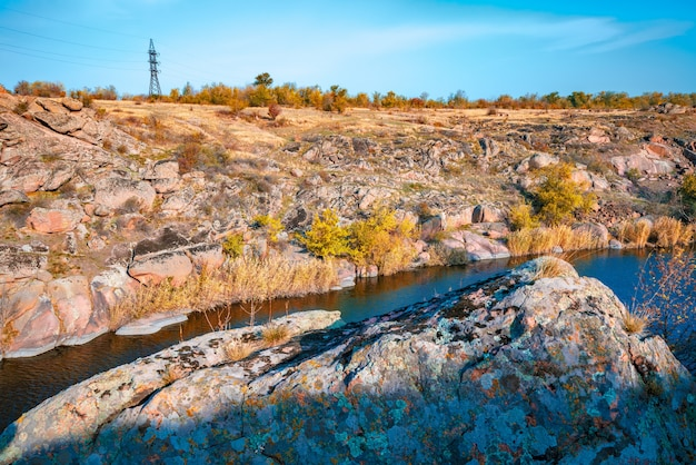 A large number of stone minerals covered with green vegetation lying above a small river in picturesque ukraine and its beautiful nature