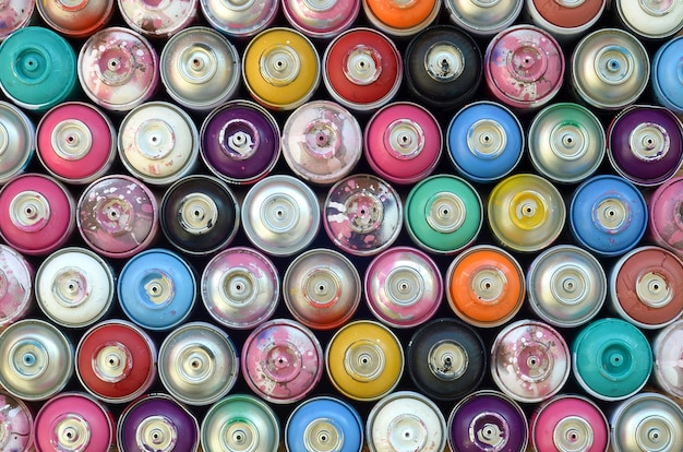 Large number of used colorful spray cans of aerosol paint, top view