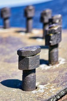 큰 너트는 도크의 콘크리트에서 돌출된 볼트에 나사로 고정됩니다. 확대