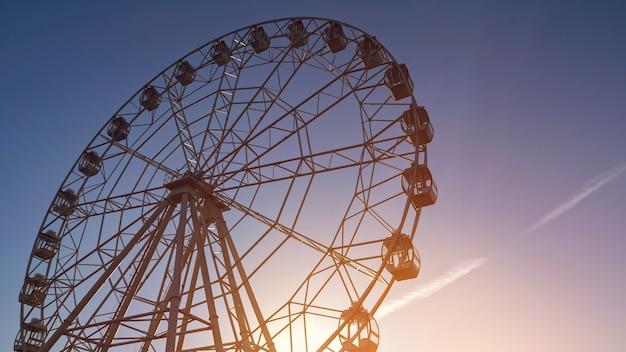 Весенним вечером в местном парке под чистым голубым небом вращается большое рабочее металлическое колесо обозрения