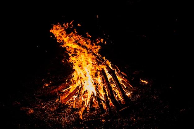 Large orange flame isolated over black background.