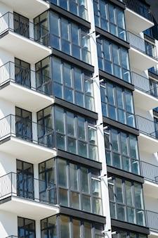 Большие панорамные пластиковые окна. фасад новостройки в доме во время строительных работ. многоэтажное здание во время строительства