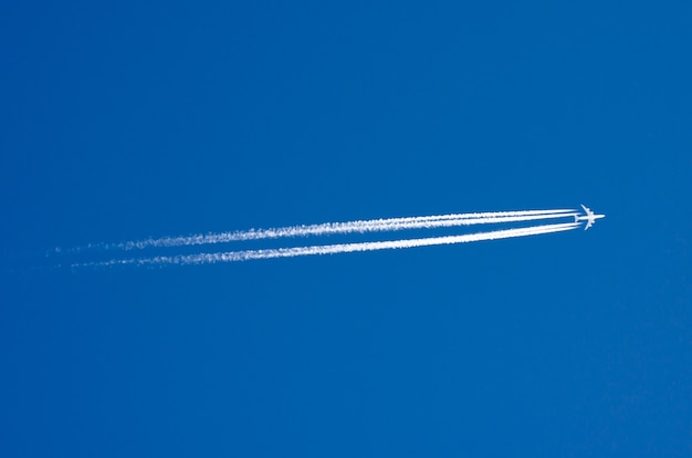 Large passenger liner and trail from an airplane in a blue sky.