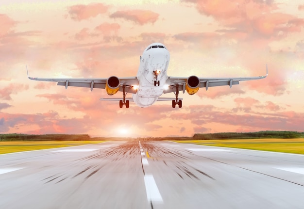 Large passenger plane take off from the runway before the light from the sunshine.