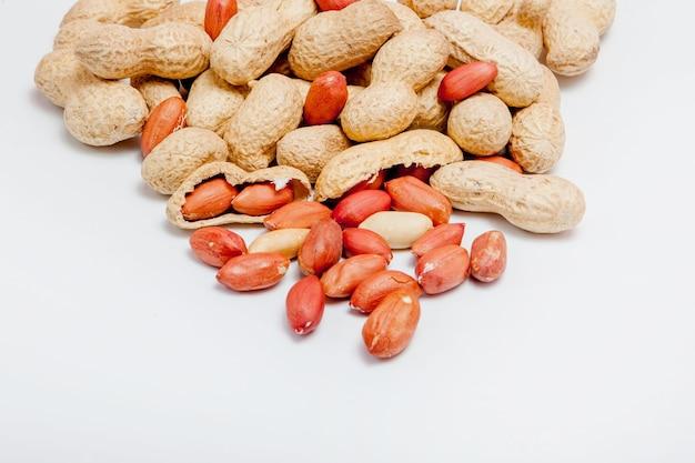 殻の中の豆の大きな皮をむいたピーナッツのクローズアップ。殻の皮をむいていないピーナッツ。成長する有機タンパク質。