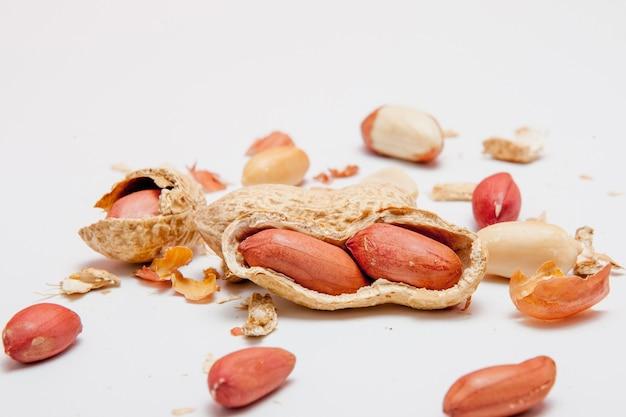 殻の中の豆の大きな皮をむいたピーナッツのクローズアップ。殻の皮をむいていないピーナッツ。ピーナッツ、背景またはテクスチャ用。成長する有機タンパク質。