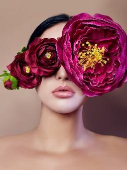Крупные пионы возле женского лица, арт-модные цветы перед девушкой, природный уход за лицом, натуральная косметика и профессиональный макияж, бежевый фон. чистота волос глаза и макияж сексуальных девушек