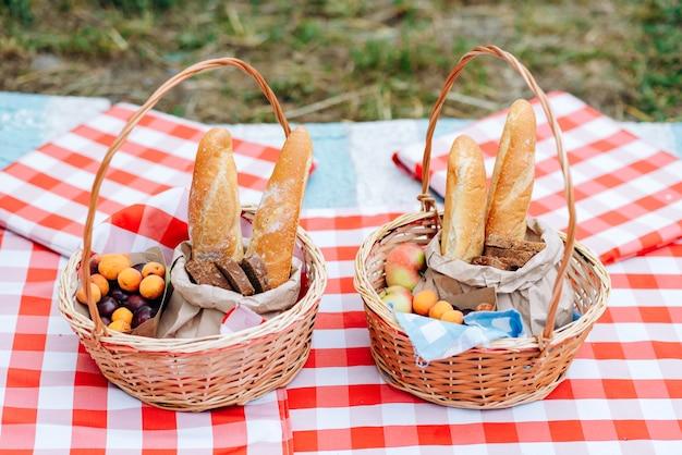 テーブルクロスの上においしい食べ物が入った大きなピクニックバスケット