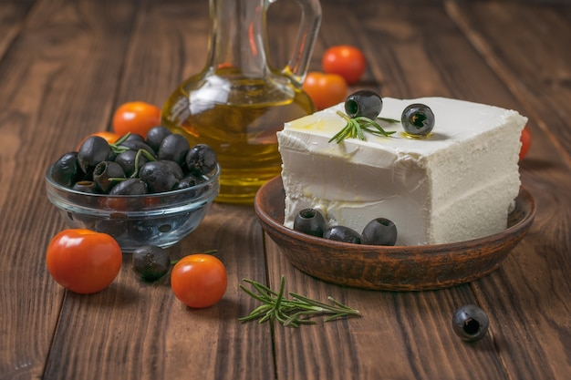 A large piece of feta cheese in a clay bowl with olives and tomatoes on a wooden table. natural cheese made from sheep's milk.