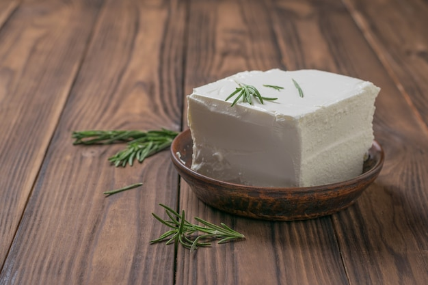 A large piece of feta cheese with rosemary sprigs on a wooden table. natural cheese made from sheep's milk.