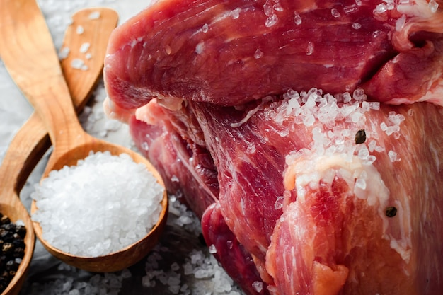 A large piece of fresh juicy meat sprinkled with salt. preparation for frying steaks.