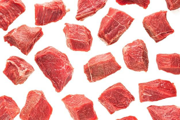 분리의 흰색 배경에 쇠고기 고기의 큰 조각. 얇게 썬 붉은 고기 큐브, 요리 배경, 레스토랑, 정육점.