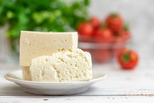 Большие кусочки сыра фета в белой тарелке и помидоры черри на свет.