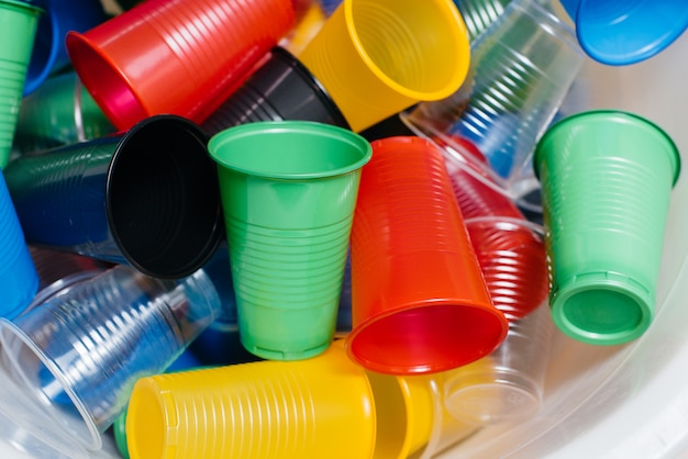 A large pile of multicolored plastic cups scattered on the floor. pollution of the environment by human waste