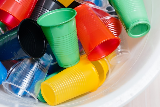 Large pile of multicolored plastic cups scattered on the floor. pollution of the environment by human waste.