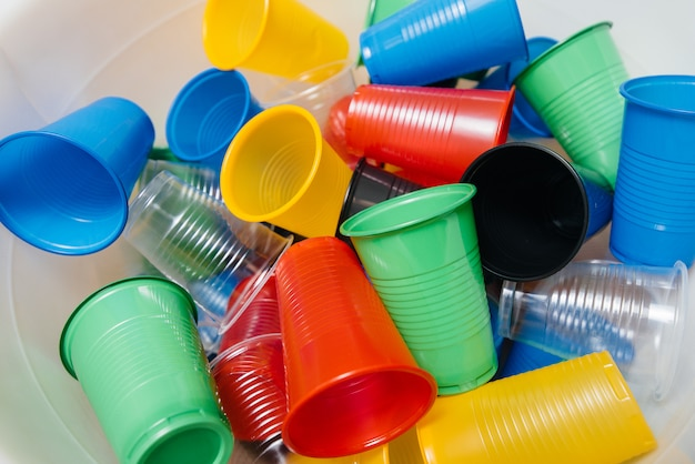 A large pile of multicolored plastic cups scattered on the floor. pollution of the environment by human waste.