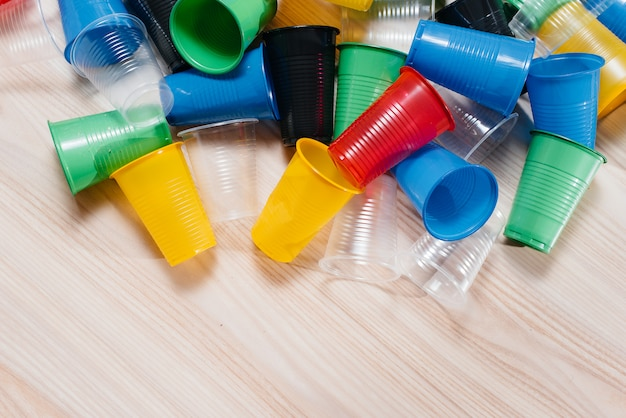 A large pile of multicolored plastic cups scattered on the floor with free space. pollution of the environment by human waste