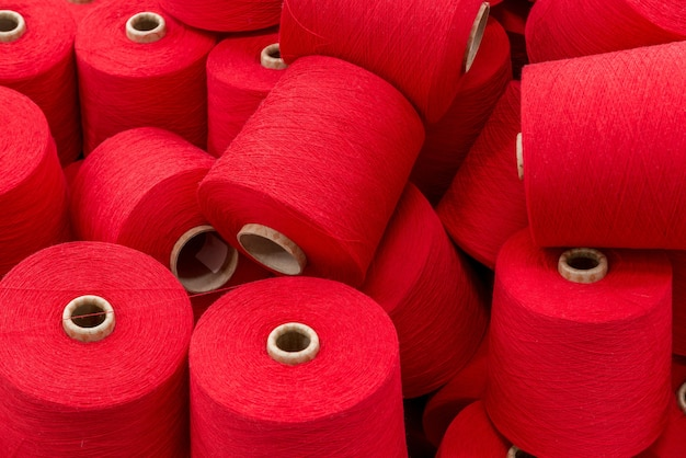 A large pile of spools of red thread. close up