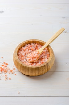 Large pink himalayan salt in a wooden bowl with a spoon on a white wooden background.