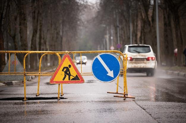 울타리와 경고 표지판이 있는 폭우와 침하 후 도로의 큰 구덩이