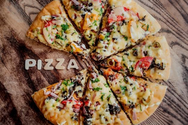 木製のテーブルに大きなピザ。飲食店。