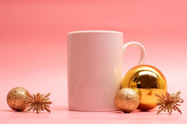 Большая обычная кофейная кружка с рождественскими украшениями вокруг нее на розовом фоне