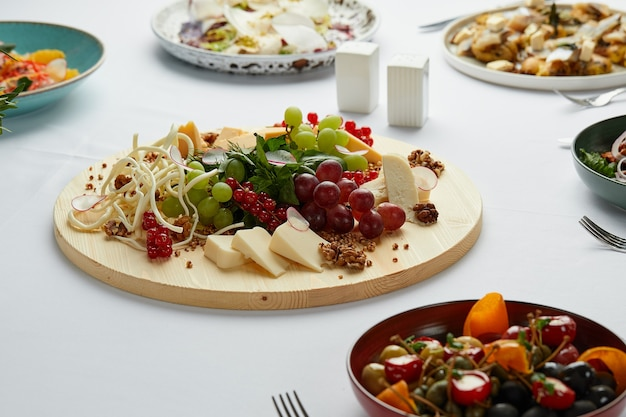 テーブルの真ん中にあるさまざまな前菜とチーズの盛り合わせの大きなプレート、テーブルの主な前菜として木のプレートにチーズを混ぜたもの。