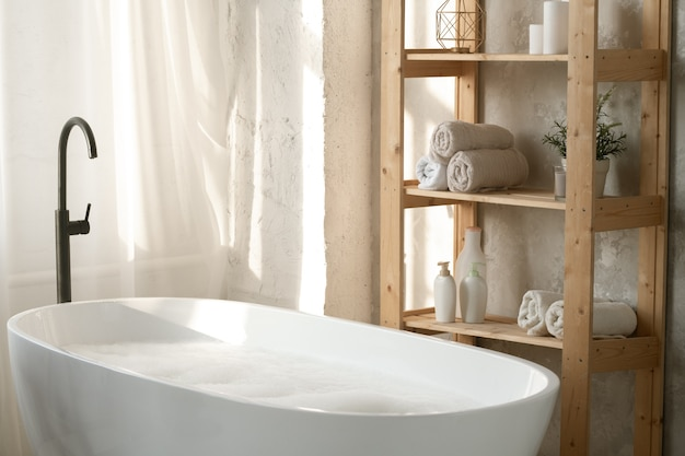 Large porcelain white bathtub filled with water and foam by wooden shelves with rolled towels and plastic jars against wall in bathroom