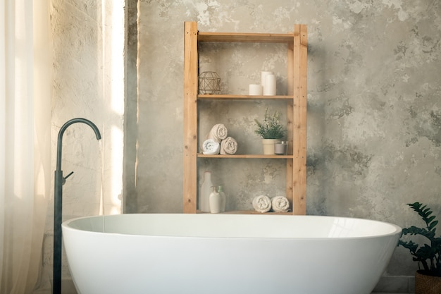 Large porcelain white bathtub and wooden shelves with rolled towels, plastic jars and candles against grey wall in bathroom