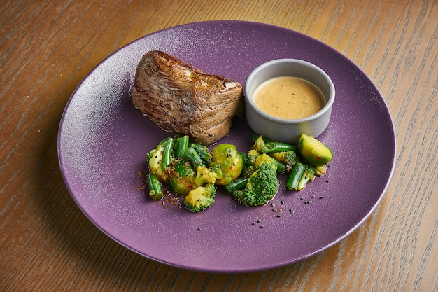 Large portion of delicious beef steak with peanut sauce and garnish of broccoli, asparagus and brussels sprouts in a ceramic plate on a wooden surface. add noise on post