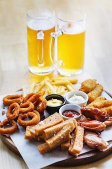 Большая порция закусок и два стакана светлого пива