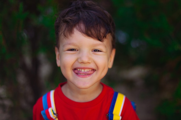 A large portrait of a cute funny boy with a slugged tongue the child shows a speech therapy exercise...