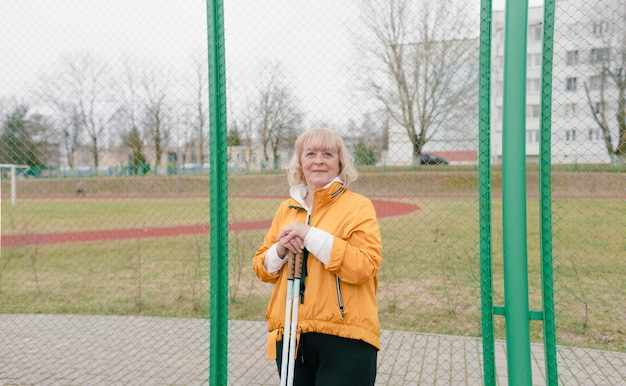 A large portrait of an elderly woman with scandinavian sticks in the stadium. beautiful athletic old woman