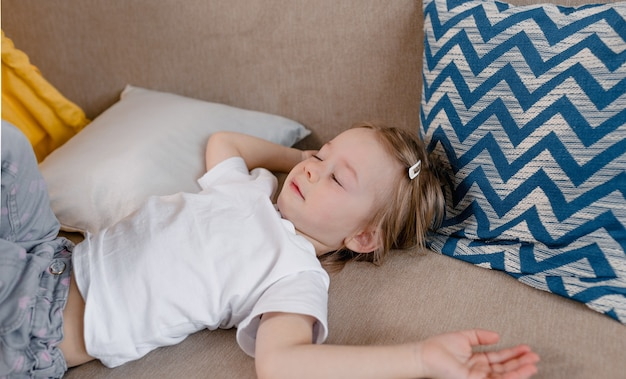 A large portrait of a little sleepy girl lying on the sofa with her hand rubbing her eyes after sleeping. awakening in children
