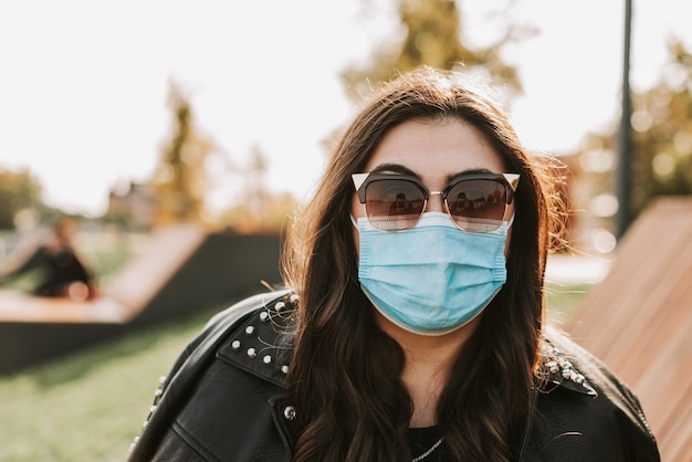 自然の公園で医療マスクと革のジャケットを着た美しい女性の大きな肖像画1