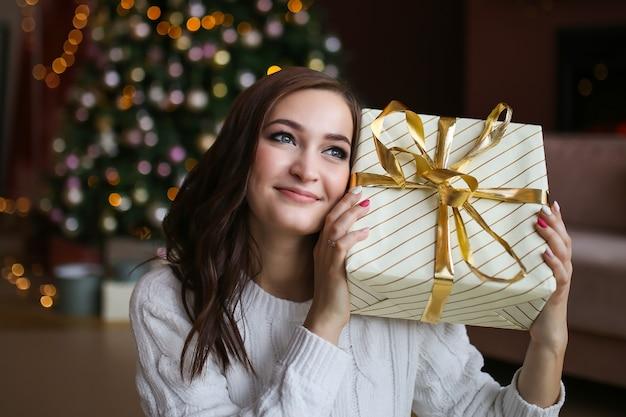 Большой портрет счастливой сладкой улыбающейся женщины с рождественской подарочной коробкой возле дерева
