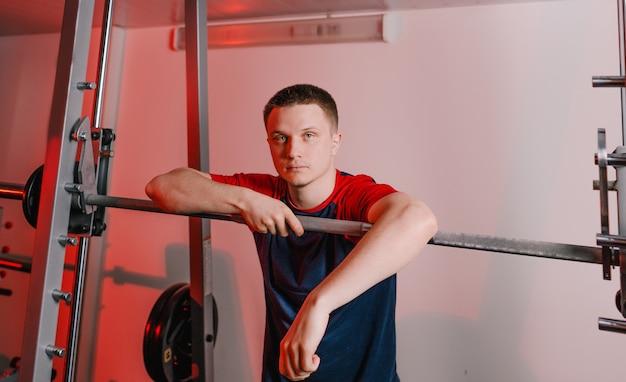 Большой портрет усталого спортсмена, стоящего возле штанги в тренажерном зале. отдыхать после тренировки