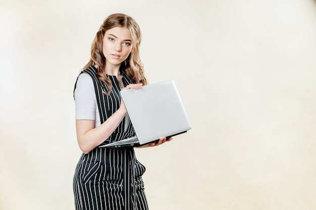 A large portrait of a pretty girl in her 20s in a formal suit and a laptop in her hands. strict piercing eyes