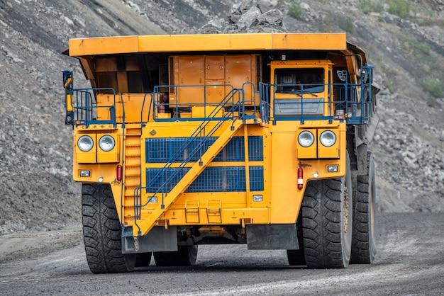 Большой карьерный самосвал. транспортная индустрия. по горной дороге едет карьерный самосвал.